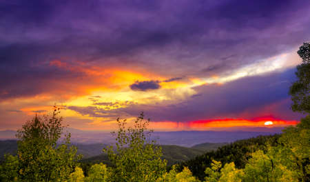 Amazing sunset over the Santa Fe Ski Basin featuring red, orange, purple, yellow, and other colors in the sky