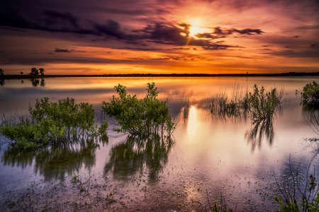 Vivid colors and reflections over serene Benbrook Lake in north Texas at dawn