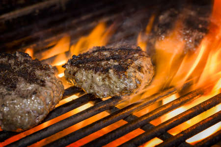 grill: Premium beef burgers flame broiled on a gas grill Stock Photo
