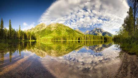 Agua perfectamente tranquilo con reflejos brillantes en Cadena Lake en Parque Nacional Grand Teton, WY