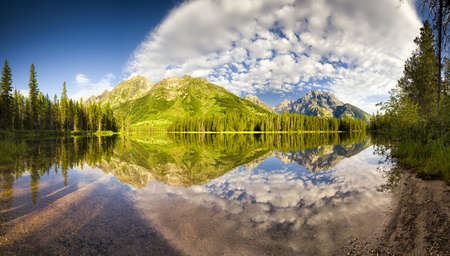 Perfectly calm water with brilliant reflections on String Lake in Grand Teton National Park, WY