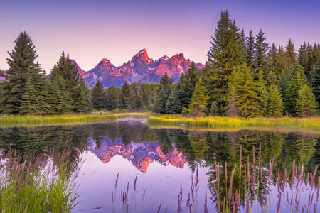 The Teton ranges reflection upon the Snake River.  Photographed at dawn at Schwabachers Landing in Grand Teton National Park, WY