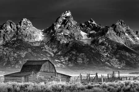Iconic John Moulton homestead with the Wyoming Tetons serving as a dramatic backdrop
