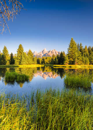 ranges: The Teton ranges reflection upon the Snake River.  Photographed at dawn at Schwabacher Landing in Grand Teton National Park, WY