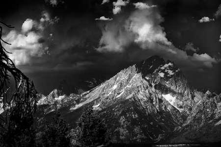 꼭대기가 눈으로 덮인: 일부 sunslight가 눈 덮인 봉우리에 통해 빛나는 테톤 범위에서 불길 한 폭풍 구름