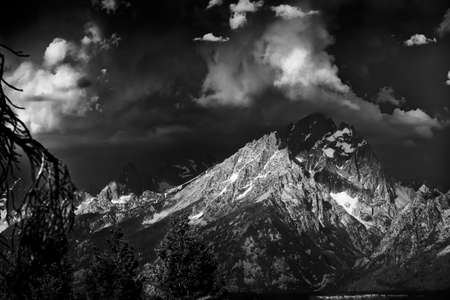capped: Ominous storm clouds over the Teton range with some sunslight shining through onto the snow-capped peaks