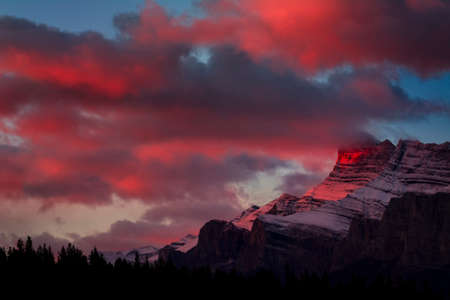 Crimson dawn light catches the jagged peaks outside of Banff, Canada