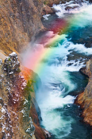Agua turbulenta que fluye en la base de Yellowstone Lower Falls, resaltado por un arco iris photo