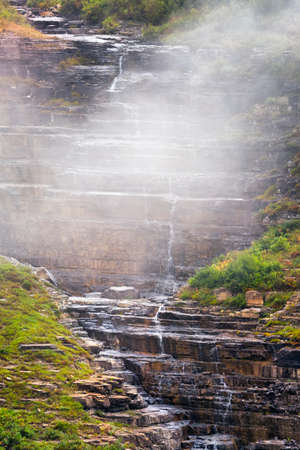 trickling: Steep trickling stream cascading down the side of a foggy mountain in Montana Stock Photo