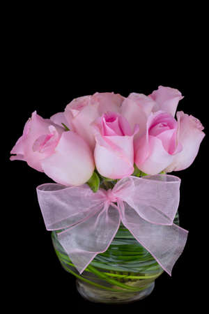 Pink roses in a vase isolated on a black background