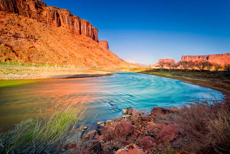 Late afternoon long exposure view of a colorful bend in the colorado River outside Moab, UT Stock Photo