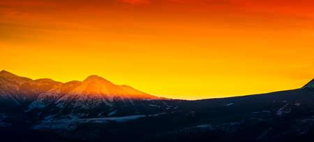 First golden rays of sunlight peeking over mountain peaks
