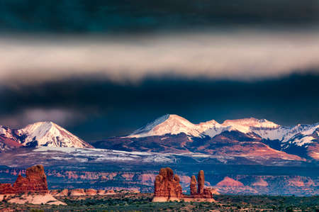 arches national park: Red sandstone hills below the snow-capped La Sal mountains in Arches National Park, Utah