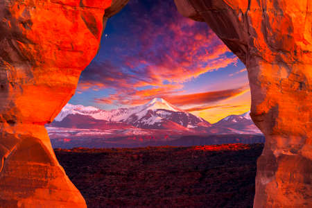 La Sal Mountains, as seen through Delicate Arch, on a colorful late afternoon in Arches National Park, Utah 스톡 콘텐츠