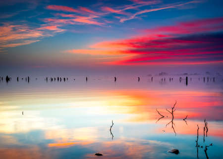 Vivid Texas sunrise over Benbrook Lake with colorful pastel reflections on the calm water