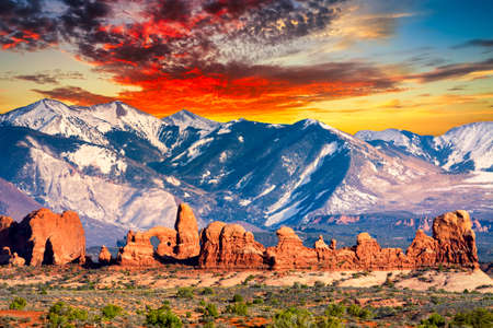 arches national park: Amazing contrast between the red sandstone hills and the cool Rocky Mountains in the background  as seen in Arches National Park, Utah