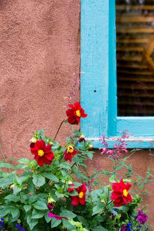 adobe wall: Fiori rossi luminosi accentuando una finestra cornice blu situato all'interno di un muro di mattoni a Santa Fe, Nuovo Messico