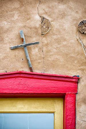 nm: Cross adorning a multicolored shop entrance in Santa Fe, NM Stock Photo