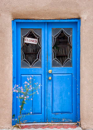fe: Unique blue door fronted by purple aster flowers in Santa Fe, NM