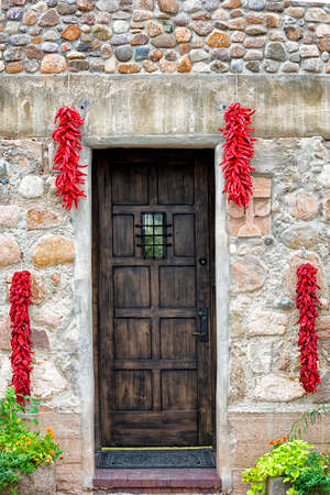 Symmetrically placed chili pepper bundles hanging from both sides of a wooden door in Santa Fe, NM