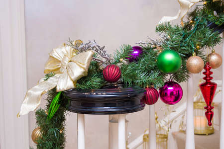 adorning: Christmas decorations adorning the railing of an elegant homes stairway