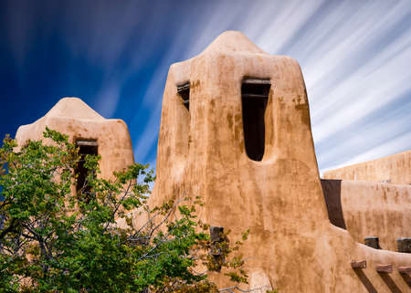 Adobe building in Santa Fe, New Mexico with cloud streaks in the sky