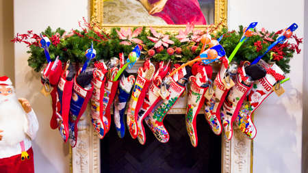 christmas stockings: Colorful Christmas stockings hanging in front of an elegant fireplace