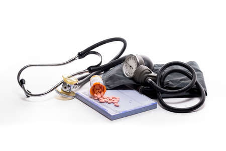 Stethoscope, blood pressure cuff, prescription pad, and pills on a white background