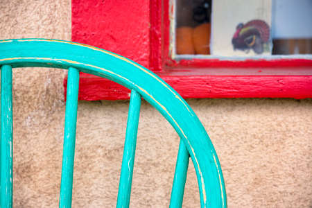 Turquoise colored antique chair sitting in front of a red window frame on Canyon Road in Santa Fe, NM