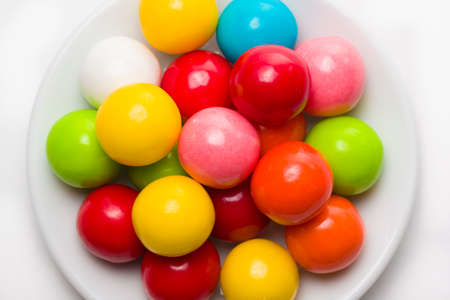 Multicolored gumballs sitting in a white plate on a white background photo