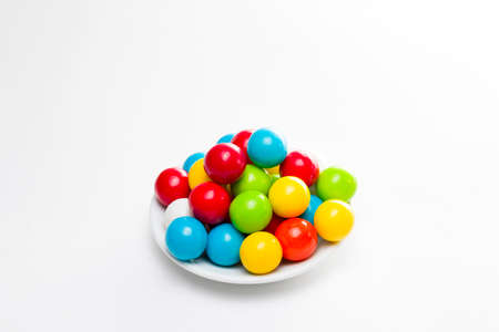 multicolored gumballs: Multicolored gumballs sitting in a white plate on a white background