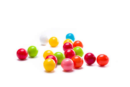 Multicolored gumballs sitting in a white background