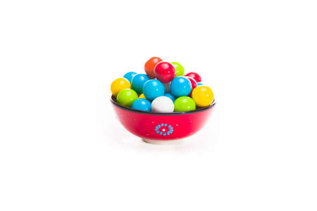 multicolored gumballs: Multicolored gumballs sitting in a red bowl on a white background