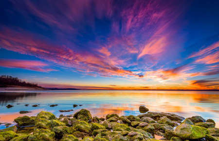Amazing multicolored sunset over Benbrook Lake in Fort worth, TX featuring vivid green mossy rocks in the foreground Stock Photo