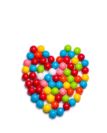 multicolored gumballs: Multicolored gumballs arranged in a heart shaped configuration lying on a white background
