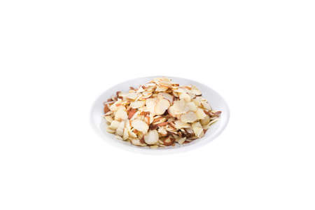 flaked: Sliced almonds in a white plate on a white background