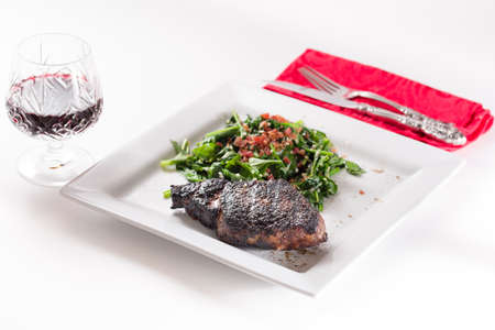 bacon bits: Prime ribeye steak served with wine and spinach sauteed in olive oil with garlic and bacon bits Stock Photo