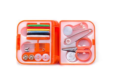 kit de costura: Pequeño kit de costura en un caso de color naranja sobre un fondo blanco