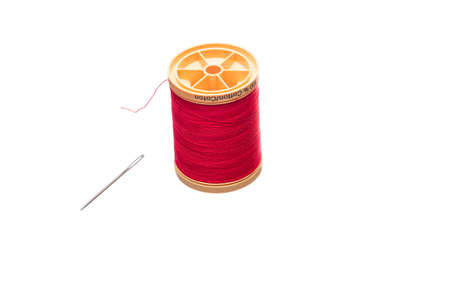 Res spool of sewing thread laying next to a needle isolated on a white background Stock Photo