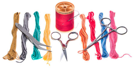 Skeins of brightly colored embroidery floss accompanied by sewing tools