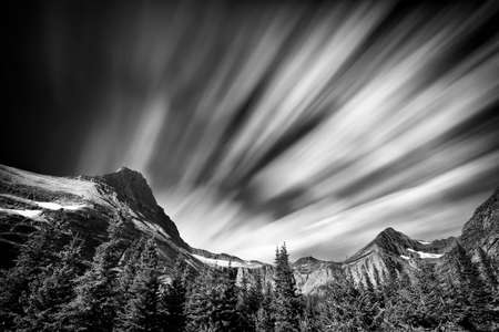 Long exposure view of the Rocky Mountains in Glacier National Park featuring dramatic streaking clouds
