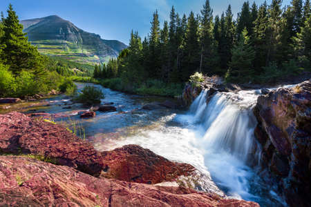 creek: Red rocks and cascading water falls in east Glacier National Park, Montana