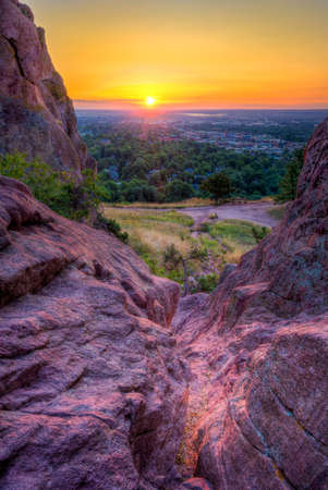 Stunning summer sunrise as viewed through the red rocks formation overlooking Boulder, Colorado Stock Photo