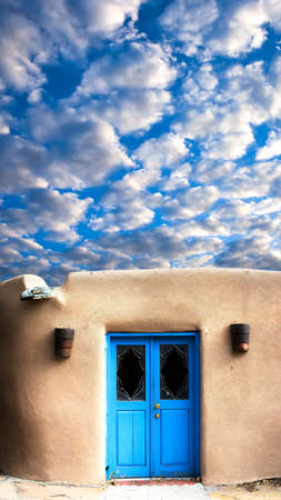 Unique blue door and a dramatic sky in Santa Fe, NM