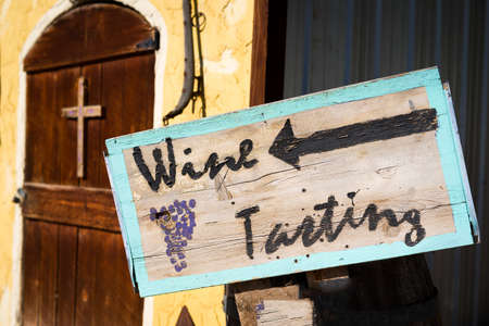 adobe: Weathered, handpainted wine tasting sign in front of an old adobe building