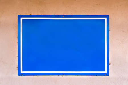 adobe wall: Blue sign with white border hanging on a weathered adobe wall in New Mexico