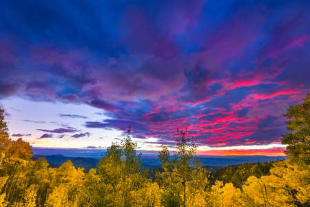 basin mountain: New Mexico fall mountain sunset  featuring golden aspens and colorful clouds Stock Photo