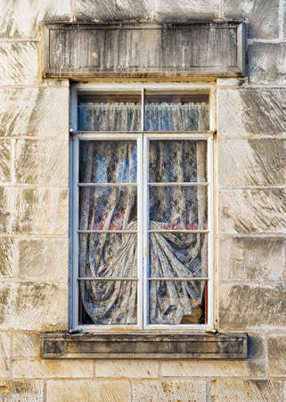 sturdy: Old metal-framed, draped window set within a sturdy limestone wall on the front of an old sanitarium in Central Texas Stock Photo