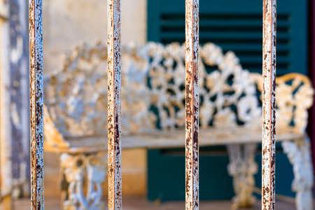rejas de hierro: Selectivo se centran en las barras de hierro delante de una antigüedad, banco oxidado Foto de archivo