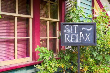 imploring: Hand-made chalkboard sign in front of a colorful gallery imploring visitors to sit and relax